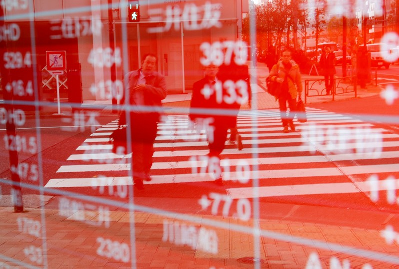FILE PHOTO: Pedestrians are reflected on an electronic board showing stock prices outside a brokerage in Tokyo
