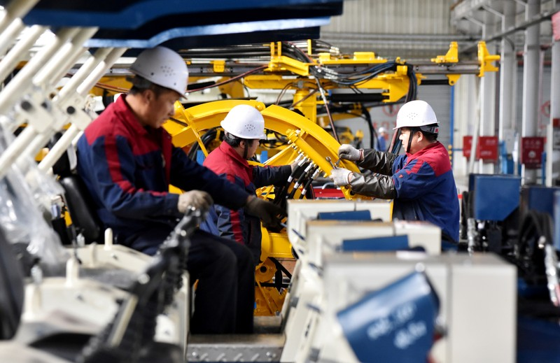 FILE PHOTO: Employees work on a drilling machine production line at a factory in Zhangjiakou