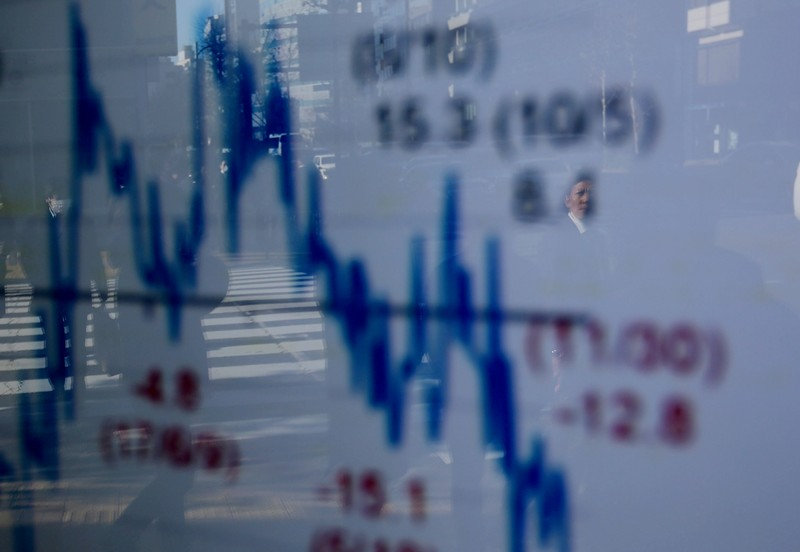 FILE PHOTO : A man is reflected on an electronic board showing a graph analyzing recent change of Nikkei stock index outside a brokerage in Tokyo