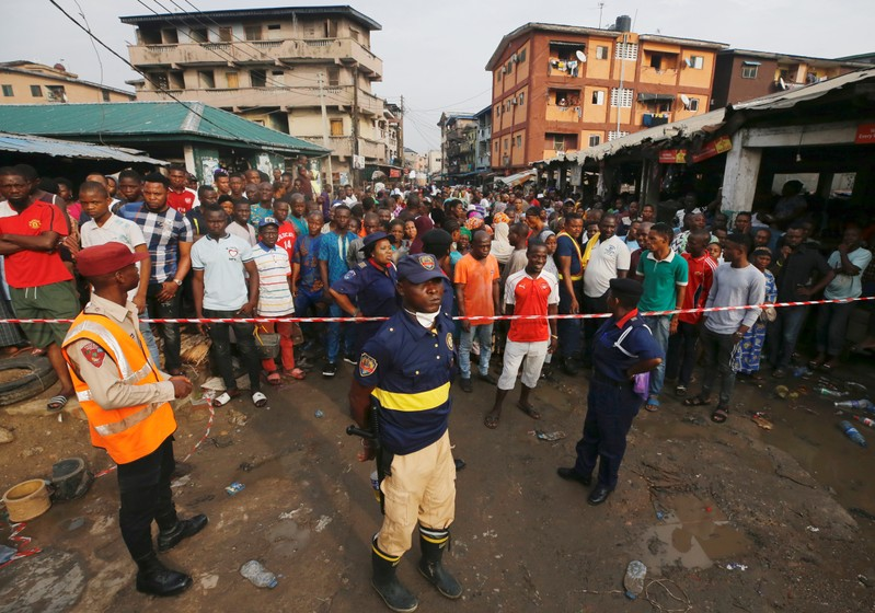 People gather outside a cordoned off area at the site of a collapsed building containing a school in Nigeria's commercial capital of Lagos