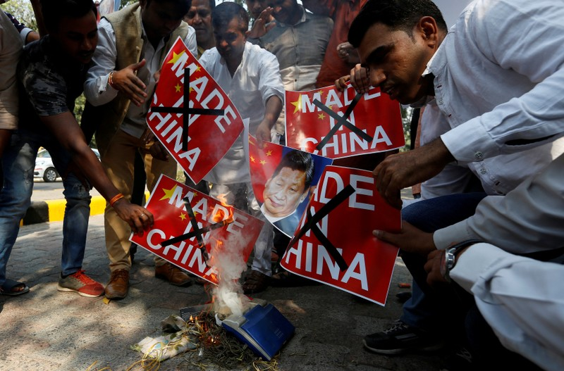 FILE PHOTO: Demonstrators burn Chinese goods and poster of Chinese President Xi, during a protest in New Delhi