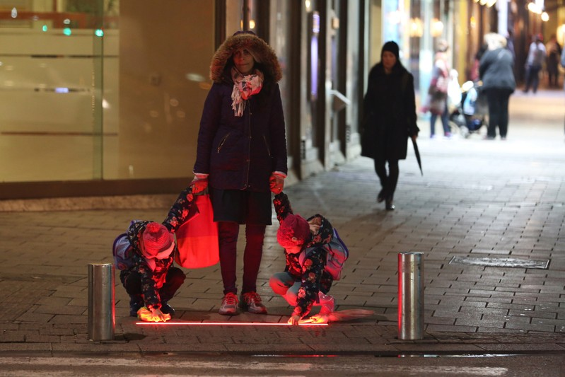 A woman holds children hands near a pedestrian crossing as they look at newly installed ground-level crosswalk lights, in Tel Aviv, Israel