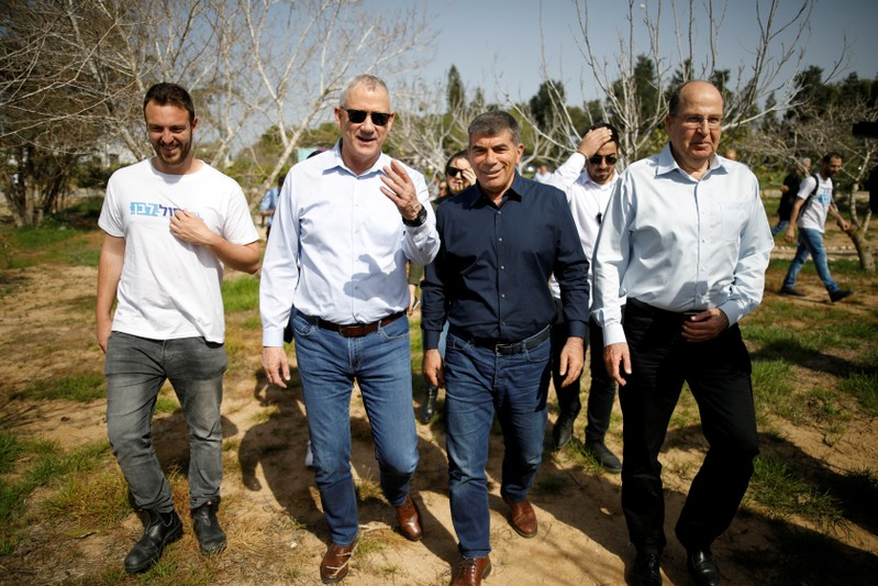 FILE PHOTO: Benny Gantz, head of the Blue and White party, walks with fellow party candidates during a visit to a kibbutz in Israel outside the northern Gaza Strip