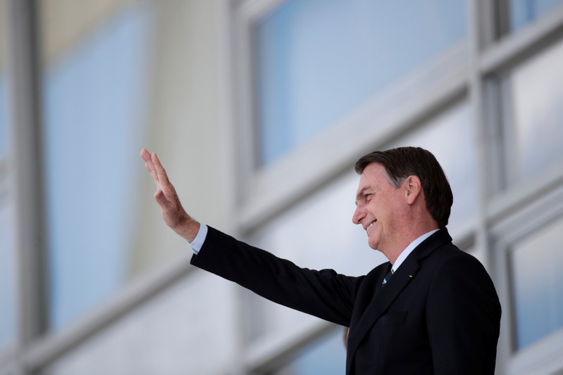 Brazil's President Jair Bolsonaro waves before a meeting with Paraguay's President Mario Abdo at the Planalto Palace in Brasilia