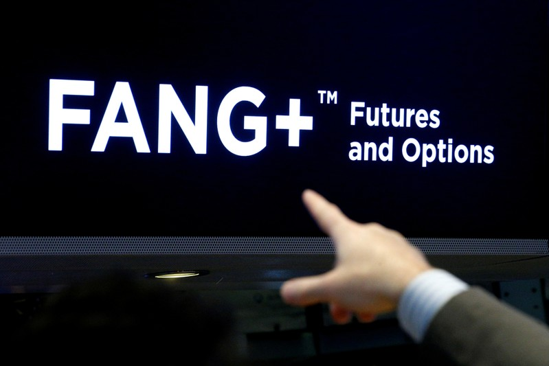 FILE PHOTO - A trader points to a screen that displays FANG+, group of highly-traded technology and tech-enabled companies, on the floor of the NYSE in New York