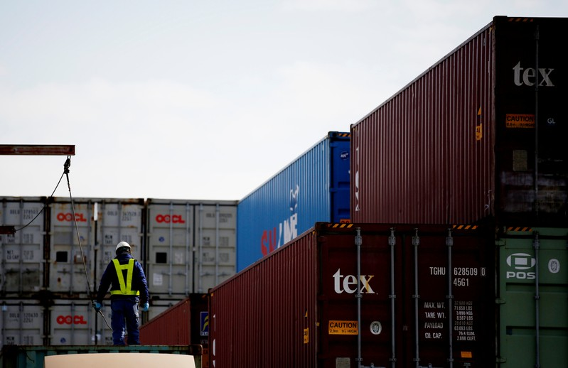 A man works to load a container on a truck at an industrial port in Tokyo