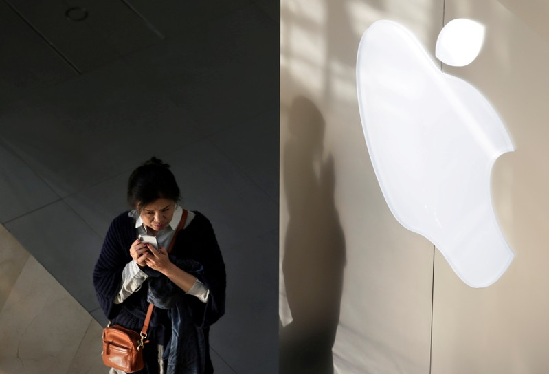 FILE PHOTO: A woman holds her phone near an Apple company logo in Beijing