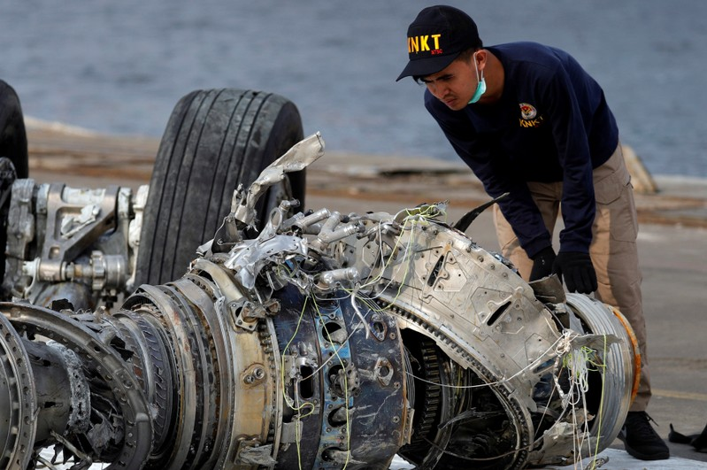 An Indonesian National Transportation Safety Commission (KNKT) official examines a turbine engine from the Lion Air flight JT610 at Tanjung Priok port in Jakarta