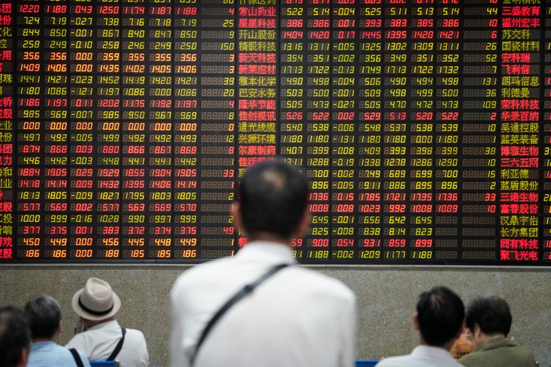 FILE PHOTO: People look at an electronic board showing stock information at a brokerage house in Shanghai