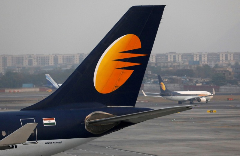 FILE PHOTO: A Jet Airways plane is parked as another moves to the runway at the Chhatrapati Shivaji International airport in Mumbai