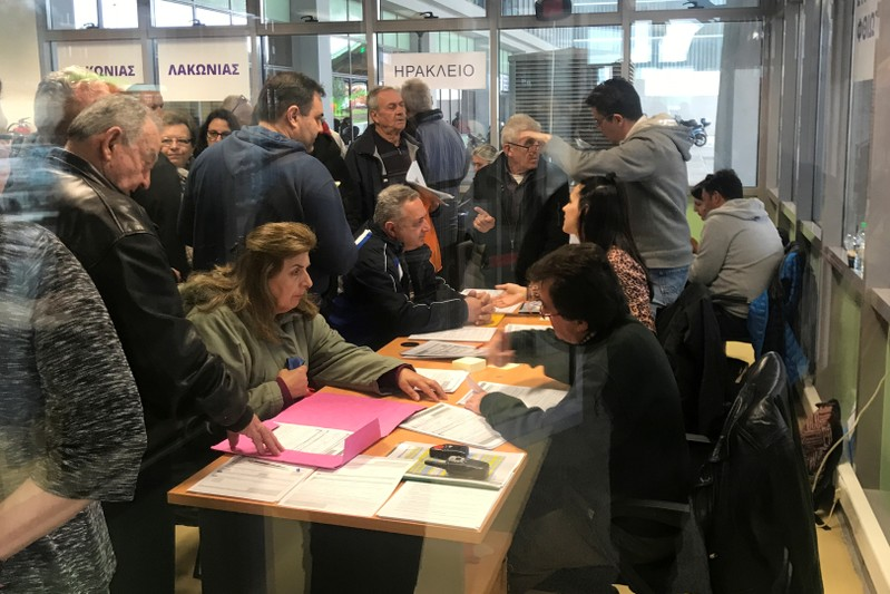 People line up to register their assets at the land registry offices in Athens
