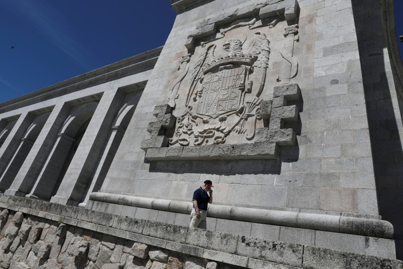 FILE PHOTO: A man walks underneath a huge Franco-era coat of arms at the Valle de los Caidos (Valley of the Fallen) monument where over 30,000 fighters from both sides of Spain's civil war are buried, in San Lorenzo de El Escorial, outside Madrid