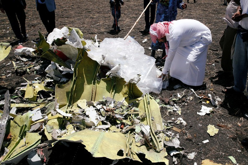 A Saudi man who's brother died in the Ethiopian Airlines Flight ET 302 plane crash, touches a debris after a commemoration ceremony at the scene of the crash, near the town of Bishoftu, southeast of Addis Ababa