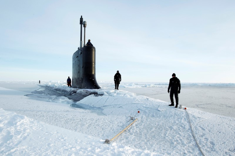 FILE PHOTO: U.S. Navy safety swimmers stand on the deck of the Virginia class submarine USS New Hampshire after it surfaced in the Arctic Ocean north of Prudhoe Bay