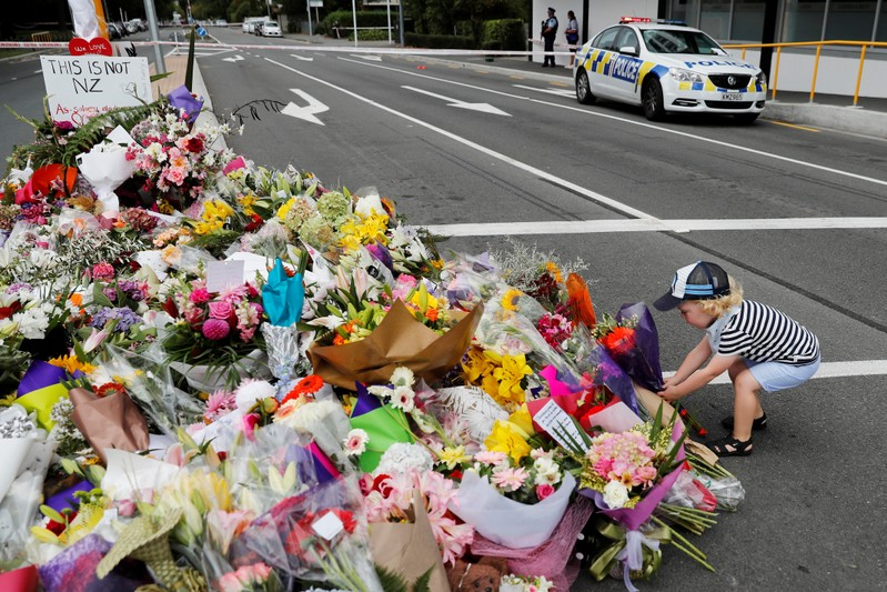 A boy places flowers at a memorial as a tribute to victims of the mosque attacks, near a police line outside Masjid Al Noor in Christchurch