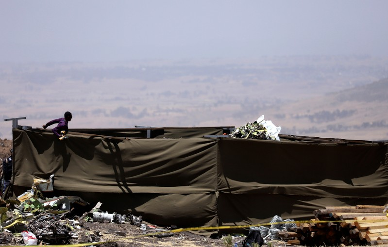 Member of a rescue team stands at the secured wreckage of the Ethiopian Airlines Flight ET 302 plane crash, near the town Bishoftu