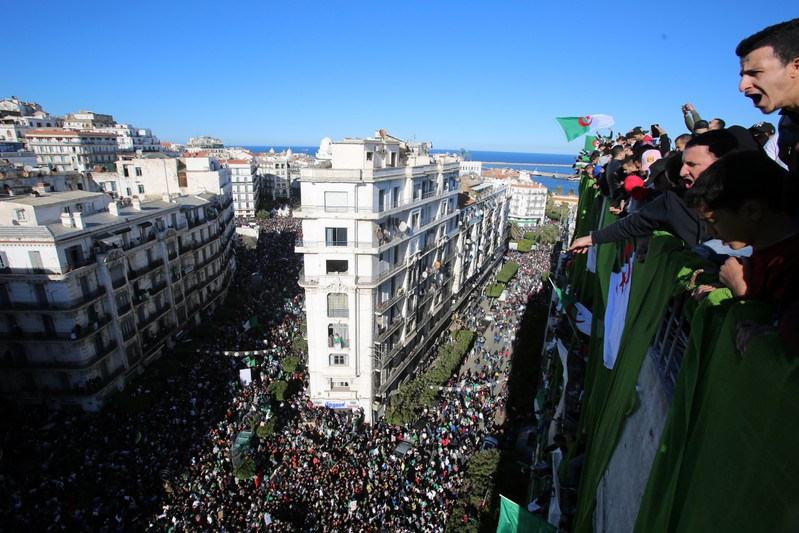 Demonstrators stand atop of a building during a protest over President Abdelaziz Bouteflika's decision to postpone elections and extend his fourth term in office, in Algiers