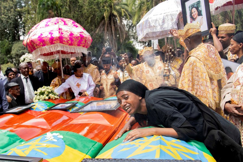A woman mourns next to coffins during the burial ceremony of the Ethiopian Airline Flight ET 302 crash victims at the Holy Trinity Cathedral Orthodox church in Addis Ababa