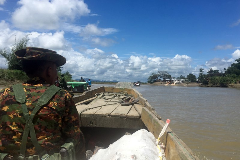 A Myanmar soldier patrols in a boat at the Mayu river near Buthidaung in the north of Rakhine state, Myanmar