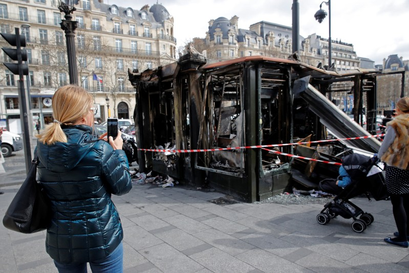 People take pictures of a newspaper kiosk burned during the last