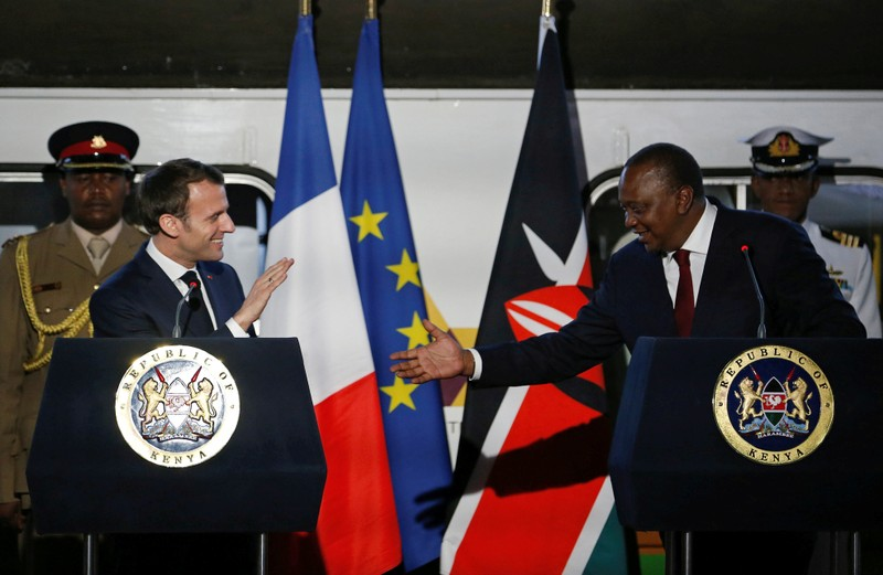 FILE PHOTO: French President Emmanuel Macron greets Kenya's President Uhuru Kenyatta as they address a news conference after touring the Nairobi Central Railway in Nairobi