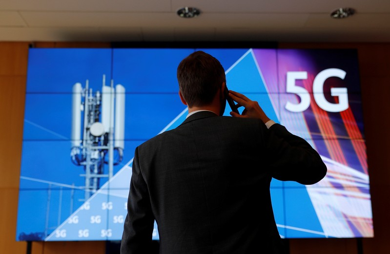 An employee of Germany's Federal Network Agency (Bundesnetzagentur) uses his mobile phone in front of a screen set up for the auction of spectrum for 5G services at the Bundesnetzagentur headquarters in Mainz