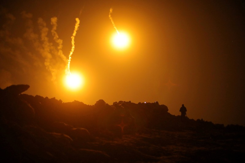 FILE PHOTO: Flares are seen in the sky during fighting in the Islamic State's final enclave, in the village of Baghouz