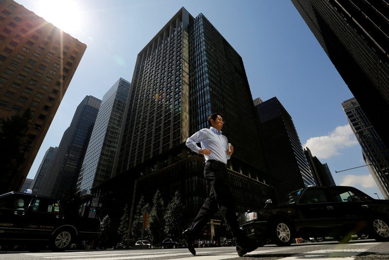 FILE PHOTO - A man runs on a crosswalk at a business district in central Tokyo