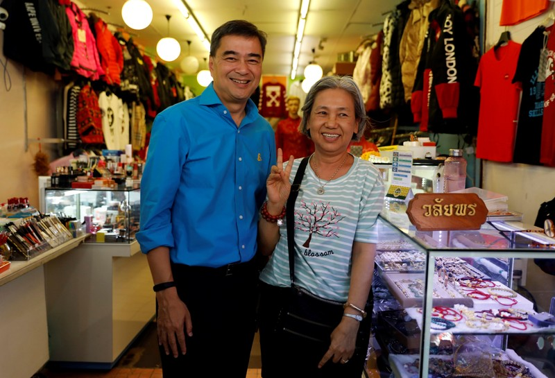 Democrat Party leader and former Thailand's Prime Minister Abhisit Vejjajiva poses with a supporter during his campaign rally in Bangkok