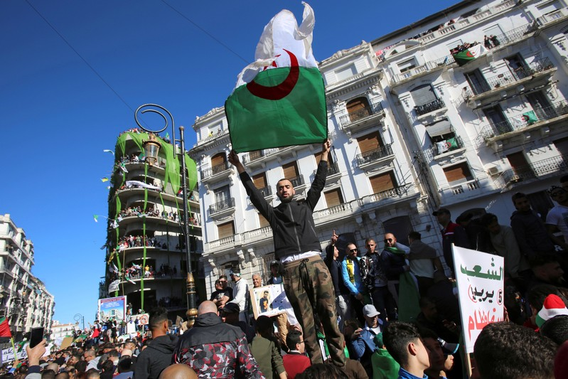 FILE PHOTO: Demonstrator carries a national flag during protest over President Abdelaziz Bouteflika's decision to postpone elections and extend his fourth term in office, in Algiers