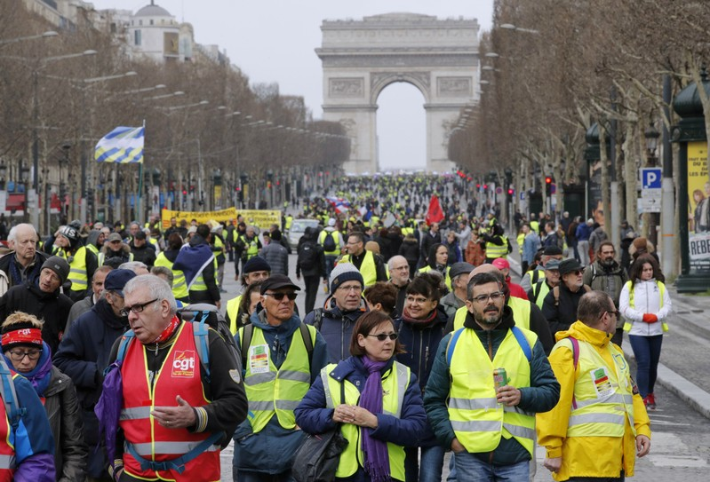 FILE PHOTO: Protesters wearing yellow vests walk down the Champs Elysees during a demonstration by the