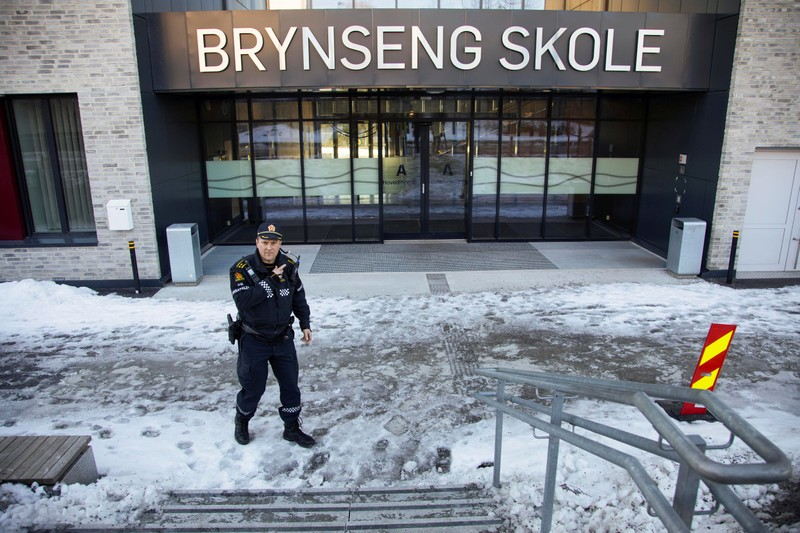 A policeman gestures outside Brynseng School after an attacker armed with a knife injured a teacher and three other staff, in Oslo