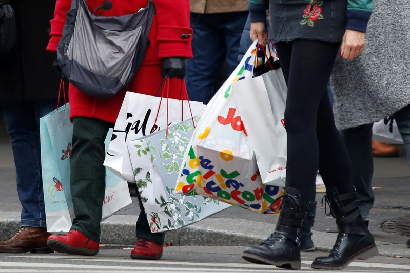 Shoppers carry shopping bags as they take care of their last-minute Christmas holiday gift purchases outside department stores in Paris