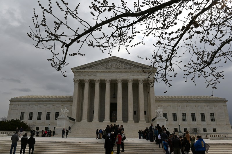 FILE PHOTO: People wait in line outside the U.S. Supreme Court to hear the orders being issued, in Washington