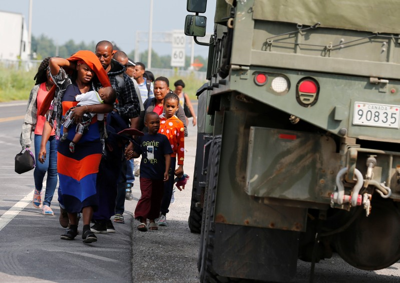 FILE PHOTO: A group of asylum seekers pass a Canadian army vehicle as they walk down the street while escorted from their tent encampment to be processed at Canada Border Services in Lacolle