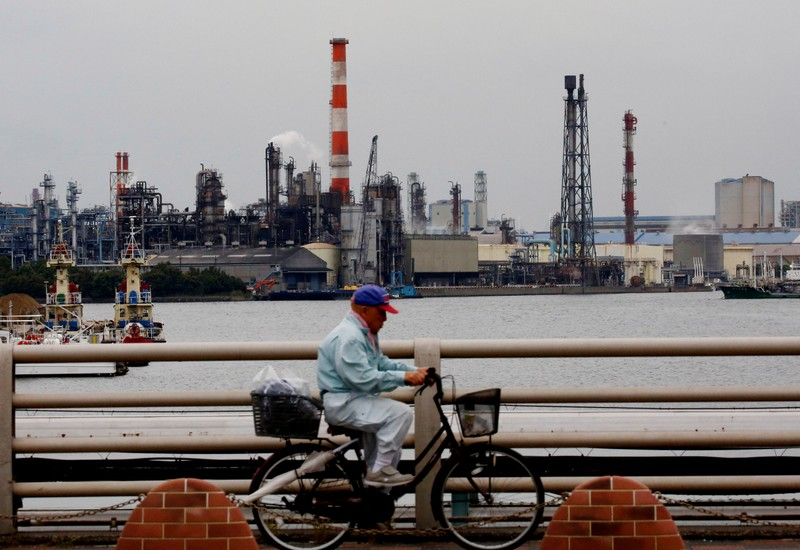 FILE PHOTO: A man cycles past chimneys of facotries at the Keihin Industrial Zone in Kawasaki