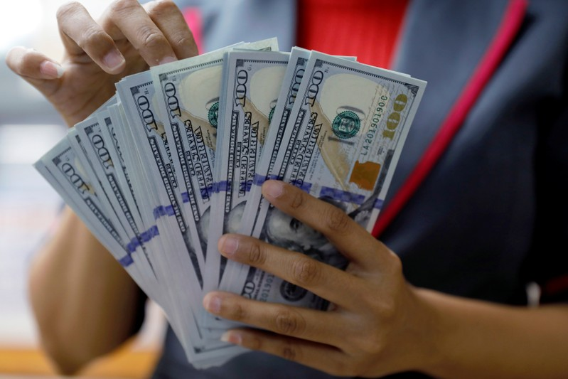 An employee counts U.S. dollar banknotes at a currency exchange office in Jakarta