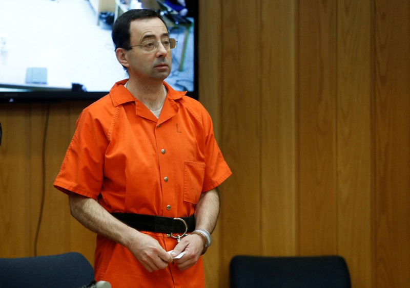 FILE PHOTO: Larry Nassar, a former team USA Gymnastics doctor who pleaded guilty in November 2017 to sexual assault charges, stands in court during his sentencing hearing in the Eaton County Court in Charlotte