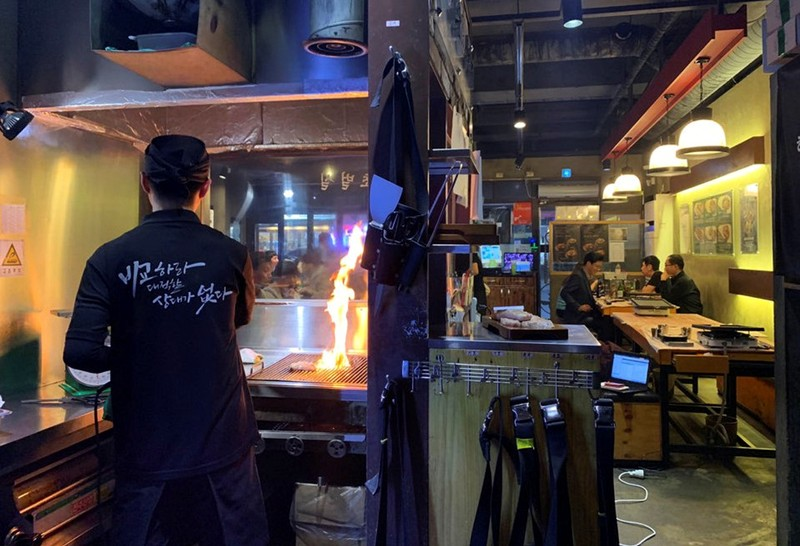 An employee roasts pork at a Korean BBQ restaurant in Seoul