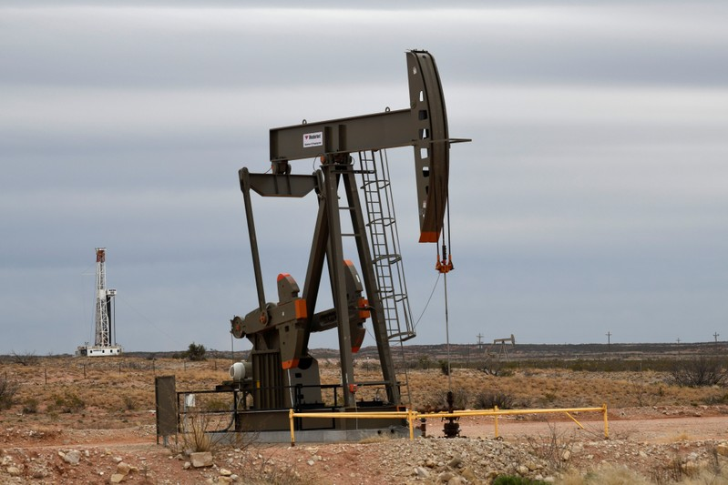 A pump jack operates in front of a drilling rig owned by Exxon near Carlsbad