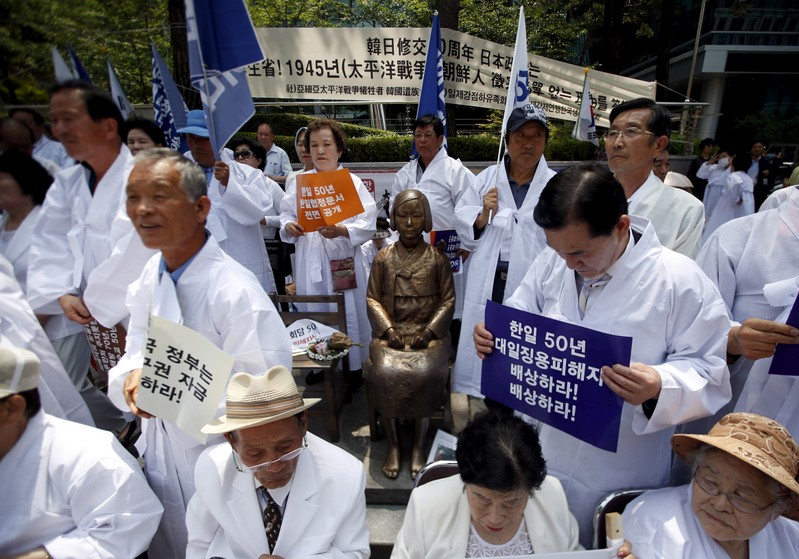FILE PHOTO: Descendants of Koreans who were conscripted to the Japanese imperial army or recruited for forced labor under Japan's colonisation surround a statue of a girl as they attend an anti-Japan rally in front of the Japanese embassy in Seoul