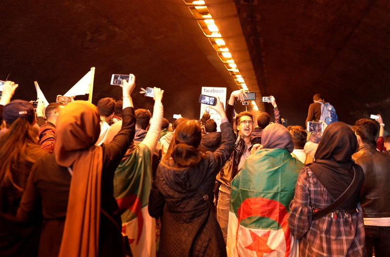 Students use their mobile phones during a protest calling on President Abdelaziz Bouteflika to quit, in Algiers