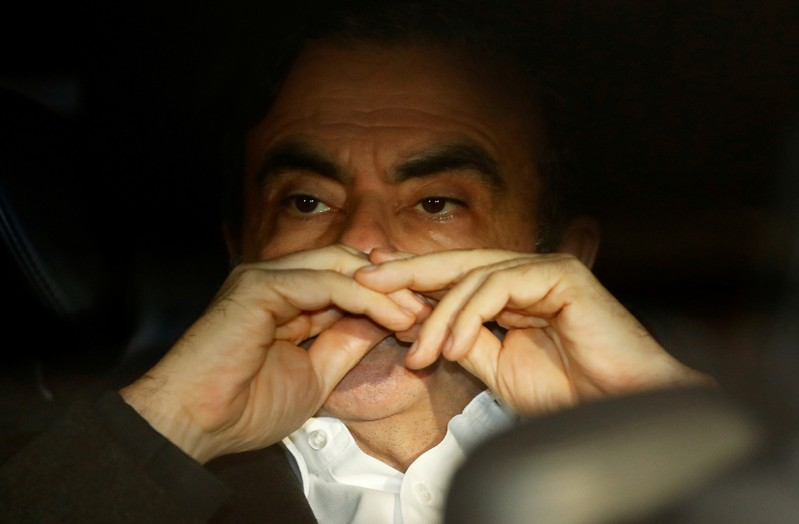 FILE PHOTO: Former Nissan Motor Chairman Carlos Ghosn sits inside the car as he leaves his lawyer's office after being released on bail from Tokyo Detention House, in Tokyo