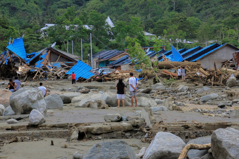 People stand as they look at damaged houses after a flash flood in Sentani, Papua