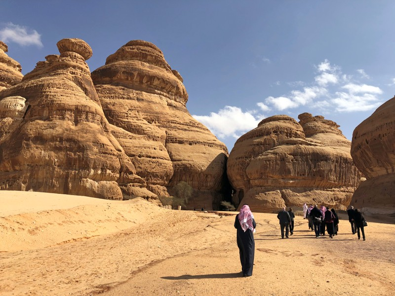 Visitors walk outside the tombs at the Madain Saleh antiquities site, al-Ula
