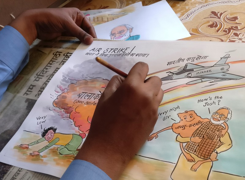 Ganesh Bhalerao, a cartoonist, draws a political cartoon inside his home in Pune