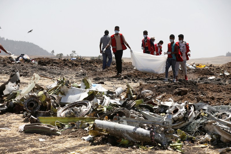 Ethiopian Red Cross workers carry a body bag with the remains of Ethiopian Airlines Flight ET 302 plane crash victims at the scene of a plane crash near the town of Bishoftu southeast of Addis Ababa