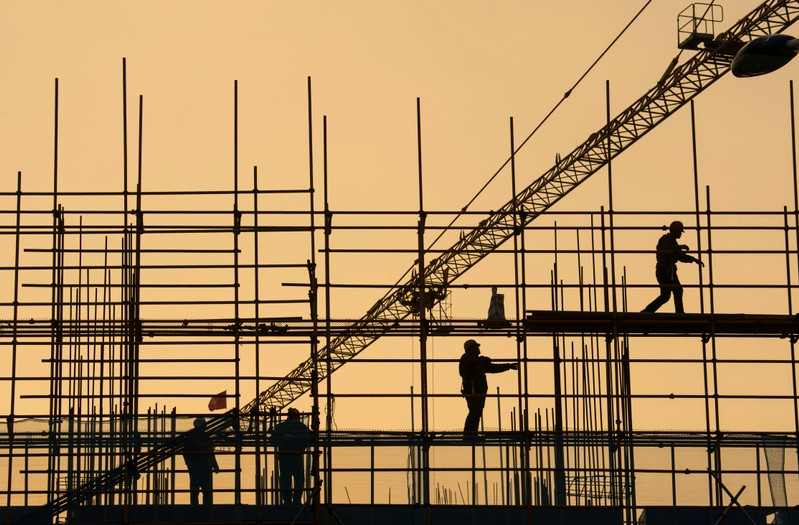 Workers are seen on scaffolding at a construction site in Nantong