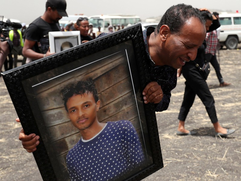 A relative carries a portrait photograph of Ethiopian Airlines pilot Yared Getachew as he mourns at the scene of the Ethiopian Airlines Flight ET 302 plane crash, near the town Bishoftu