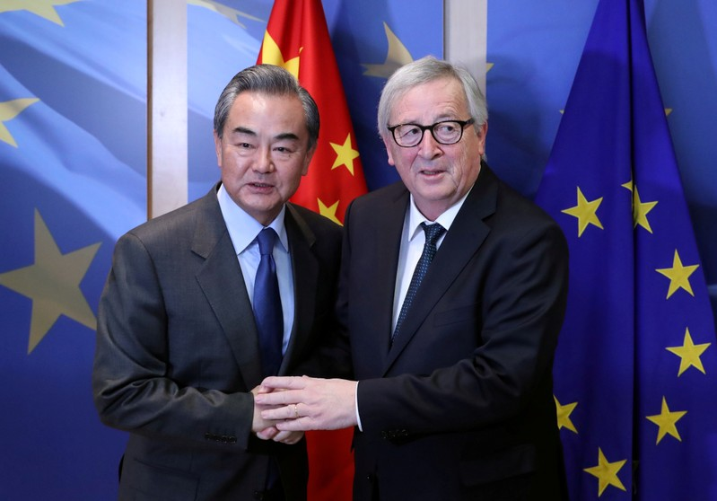 FILE PHOTO: Chinese Foreign Minister Wang Yi is welcomed by European Commission President Jean-Claude Juncker ahead of a meeting in Brussels